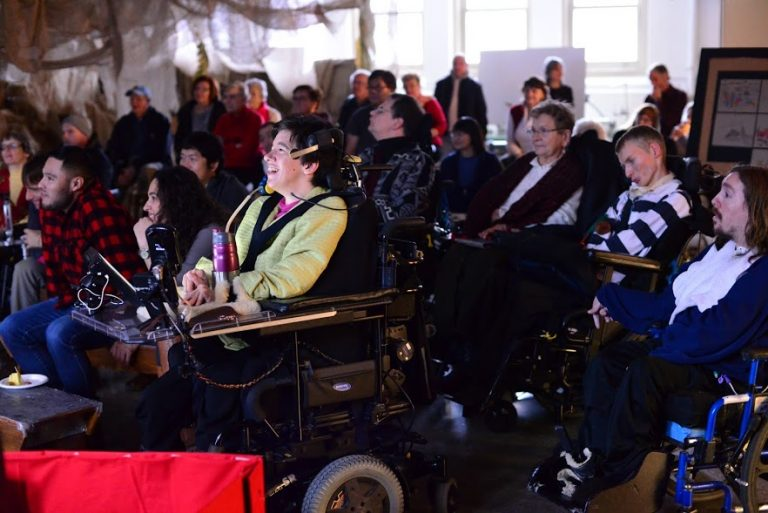 Group of wheelchair users and audience members sit and watch film together in small room with brown fabric