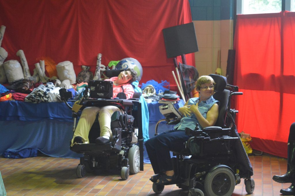 woman in blue shirt and woman in pink shirt sitting in wheelchairs in front of table with props on them