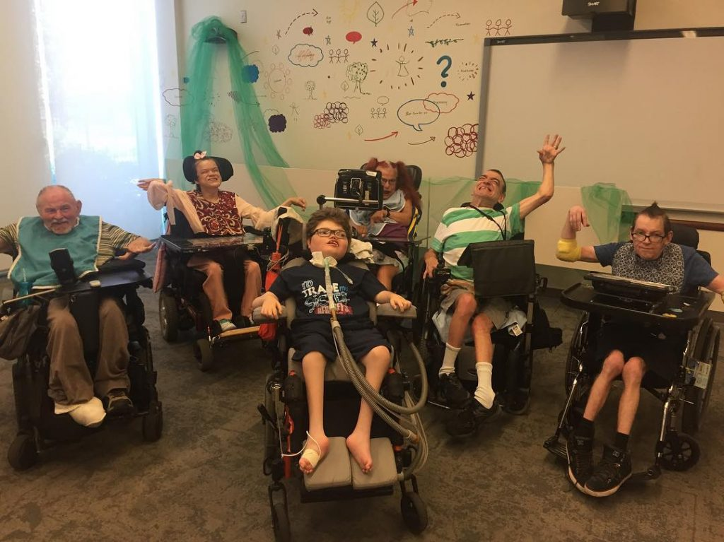 young boy sitting in wheelchair poses and smiles with five wheelchair users