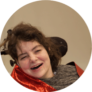 Woman wearing grey shirt and red satin around shoulders sitting in wheelchair laughs