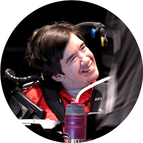 Woman in red shirt sitting in wheelchair looks up and smiles