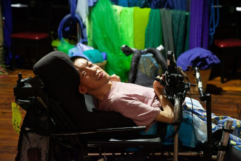 man in pink shirt sitting in wheelchair in front of fabric hanger with blue-green fabric