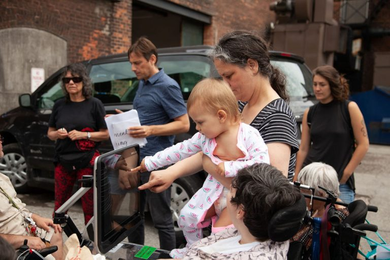 woman in striped black and white tee holds baby who touches screen attached to woman's wheelchair