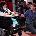 man in blue shirt crouches and smiles at woman in white shirt sitting in wheelchair who smiles back