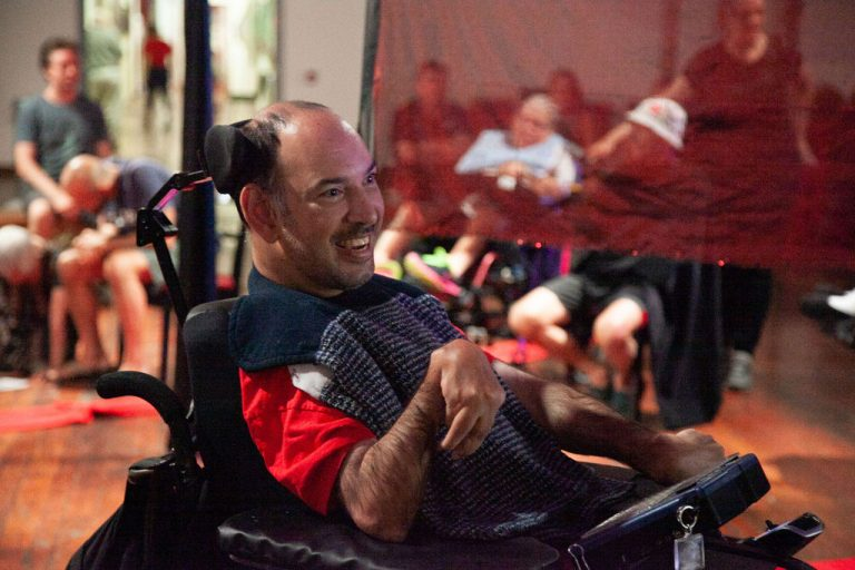 man in red shirt and striped blue scarf sitting in wheelchair smiles