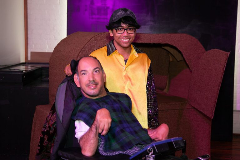 Man wearing white shirt and blue and green plaid scarf poses and smiles with young man wearing yellow and sequined jacket and glasses and cap